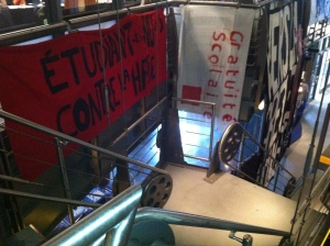 """Étudiant.e.s nu.e.s contre la hausses"" & ""Gratuité Scolaire"" banners hung from bannisters at the top of the stairs at Cinéma Excentris"