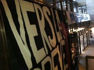 "The enormous ""Vers la grève sociale!"" banner that measures 5.5m high X 4.8m wide was hung from bannisters in the hallway leadng to the stairs at Cinéma Excentris."