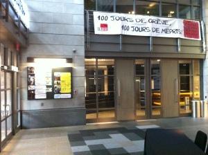 """""""100 jurs de grève, 100 jours de mépris!"""" by the CLASSE is hung from bannisters adjacent to the main entrance to face the theatre entrance where the documentary film """"Carré rouge sur fond noir"""" at Cinéma Excentris."""