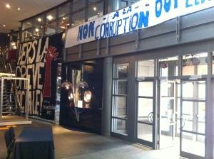 """""""Non à la corruption. Oui à l'éducation"""" is hung from bannisters above the main entrance at Cinéma Excentris."""